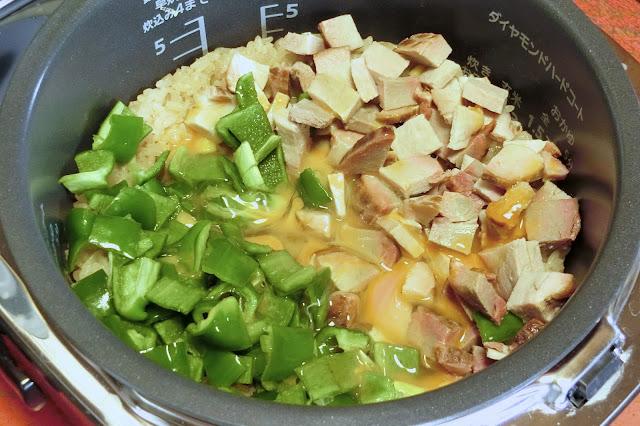 炊けたらすぐピーマン、焼き豚を米の上にのせ、溶き卵をまわしかけたら混ぜずにふたをし、10分蒸らします。