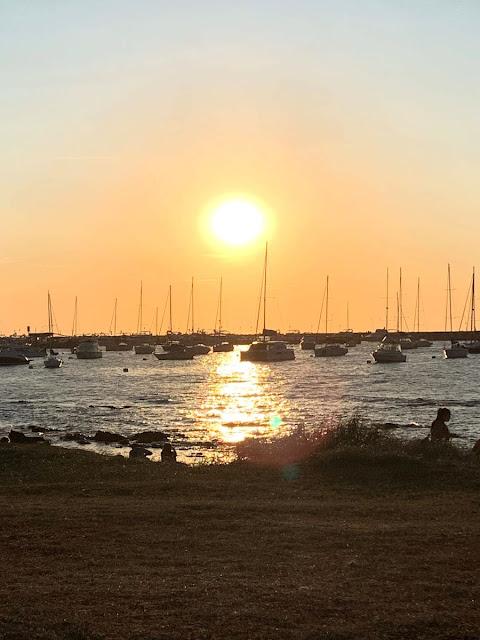 por do sol em um porto cheio de barcos ancorados