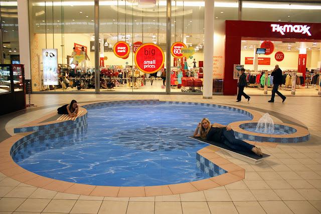 Bir alışveriş merkezi zemininde bir yüzme havuzunu gösteren kaldırım sanatı resmi