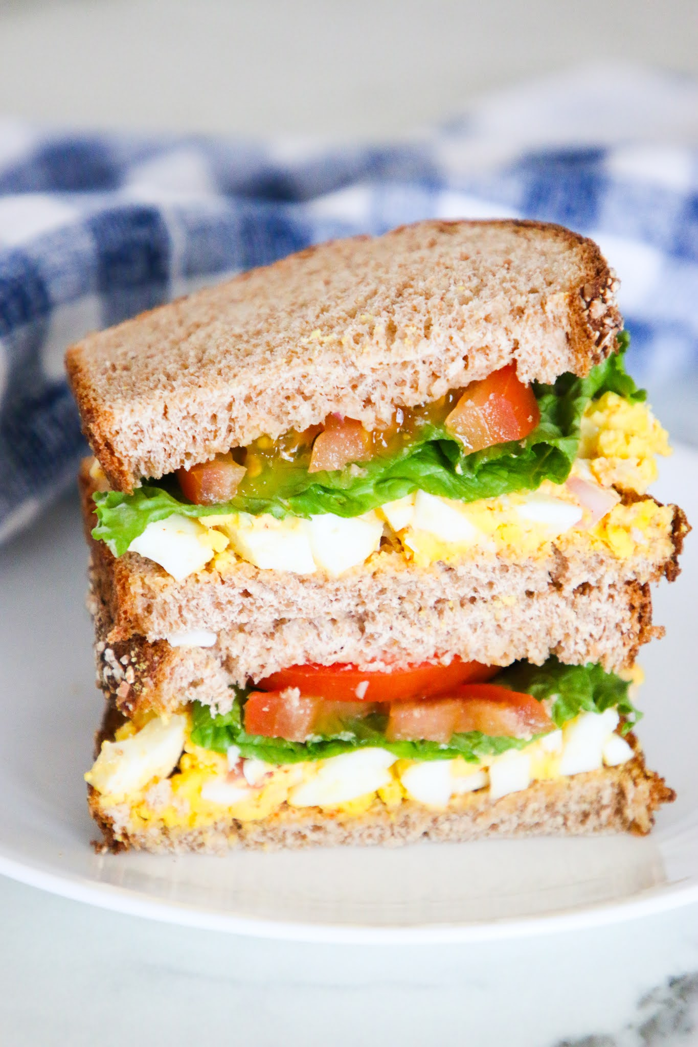 Two halves of an egg salad sandwich stacked together on a white plate with a blue dishtowel in the background on a marble table