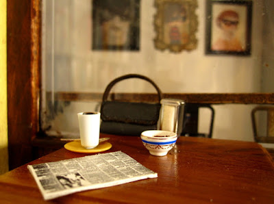 Modern one-twelfth scale miniature table with coffee, a newspaper and a handbag on it outsise a hole-in-the-wall cafe.
