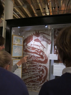 Photograph of a group of students looking at a painting by Aboriginal artist Yirawla. The painting is on bark and is of the Rainbow Snake, done in the 'X-ray style' of painting