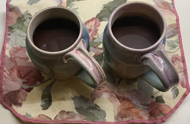 Photo of two large mugs of keto hot chocolate, sitting on a pink and ivory flowered cloth placemat