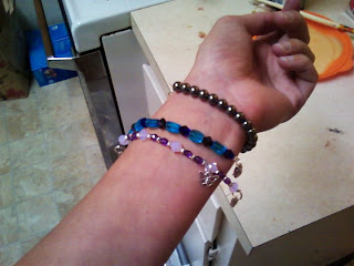 Fair wrist proudly displaying a grey hematite bracelet, a blue and teal bracelet, and a purple, lavendar, and silver bracelet