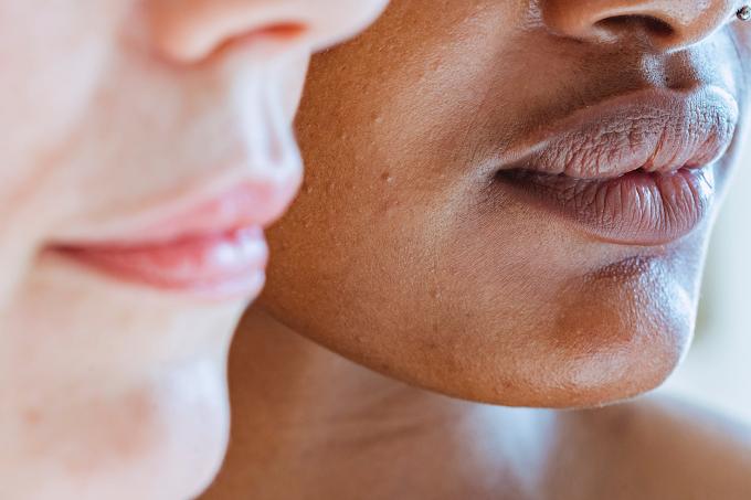 Rostos de duas mulheres mostrando só um pedaço do nariz, a boca e o queixo. A mulher da esquerda é caucasiana e está desfocada. A da direita é preta e está focada.