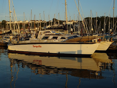 white boat in marina with calm reflective water