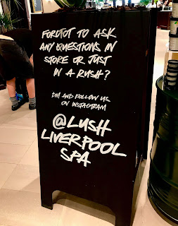 A black rectangular sign with @lushliverpoolspa in white font on a bright background