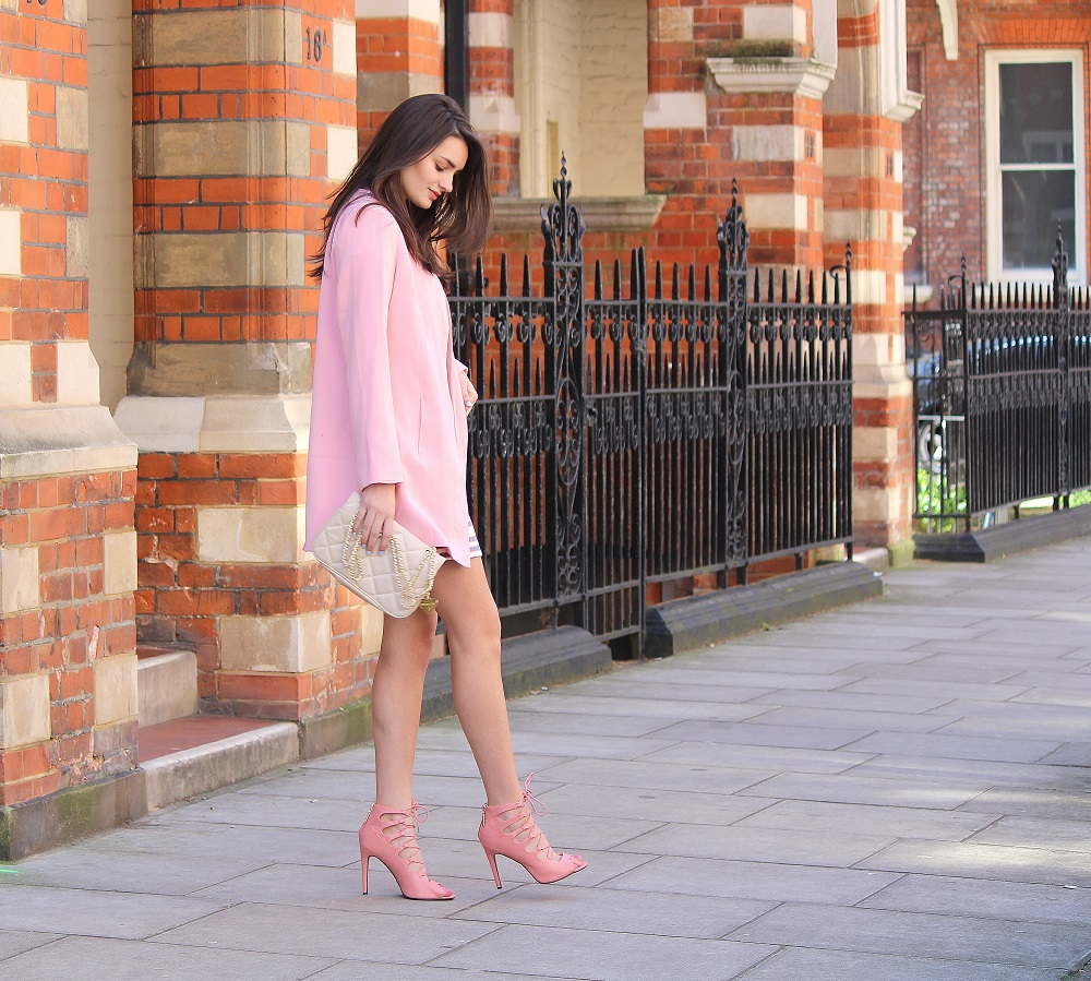 peexo fashion blogger wearing pink striped shift dress for wedding season spring with pink lace up heels and coat
