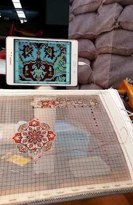 A very fine miniature carpet in progress, with the pattern on a tablet above it.