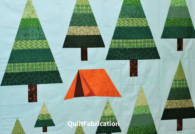 green striped trees with an orange tent for a quilt pattern by QuiltFabrication