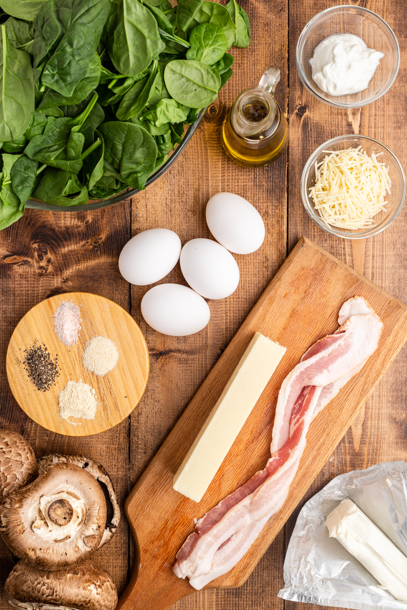 Photo of the ingredients needed to make Keto Spinach and Egg Stuffed Mushrooms on a wooden table.