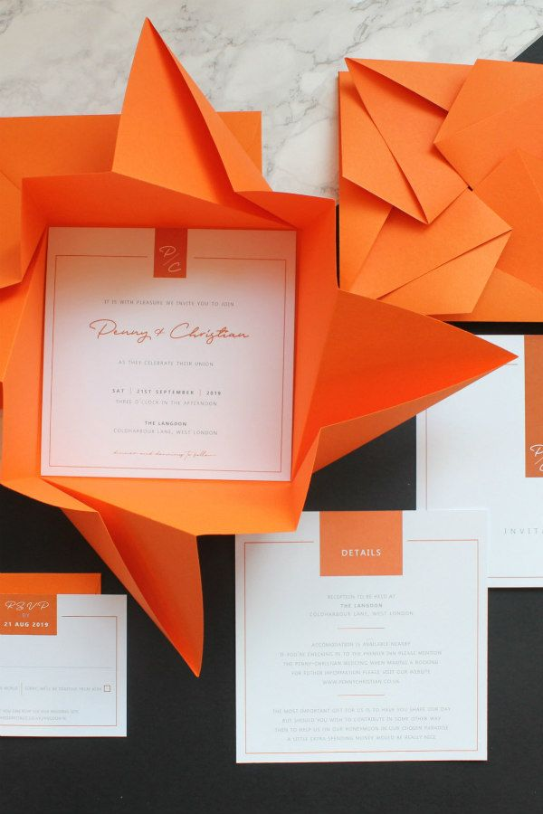origami folder encasing wedding invitation with accompanying wedding stationery