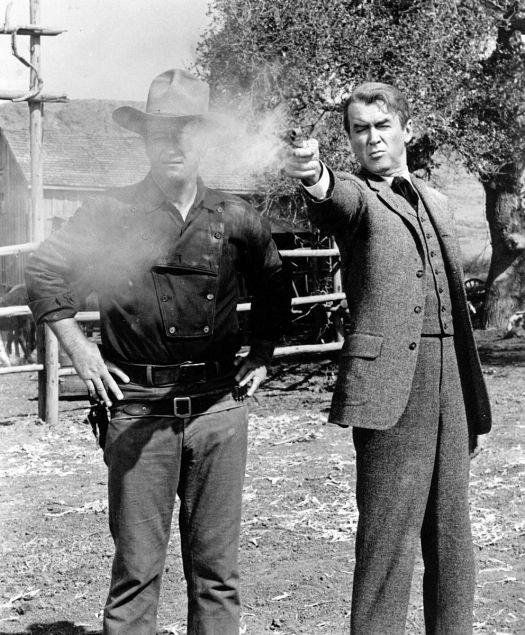John Wayne, with James Stewart shooting a gun