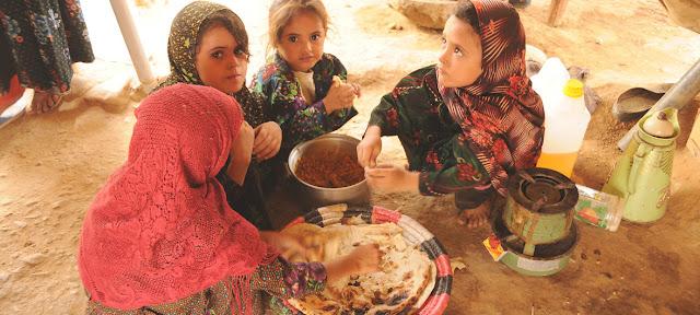 Niñas desplazadas en el campamento de Al-Mazraq en Yemen comparten una simple comida de pan y legumbres preparada por sus madres.PMA/Abeer Etefa