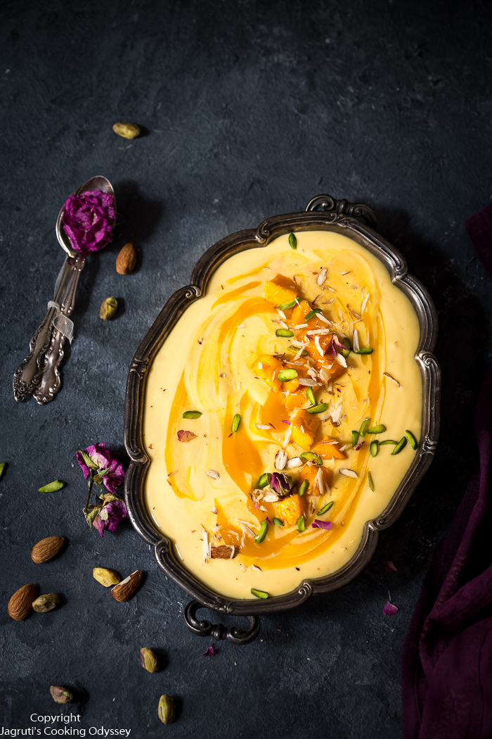 This pale orange colour indian style yogurt dessert is served in a bowl and garnished with green pistachio