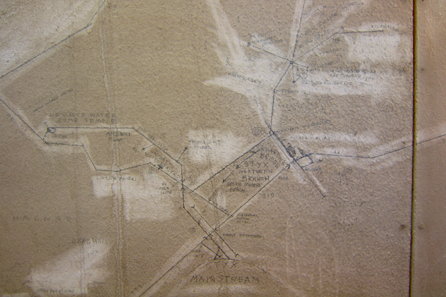 a drawing of a map on a worn wall, with names like Styx River written on the map that depicts a sewer system in central Helsinki.