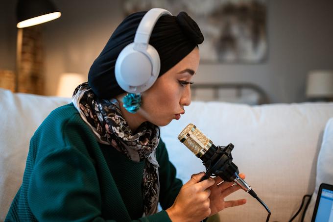 Mulher com headphone branco, de frente para um computador e falando em um microfone de estúdio