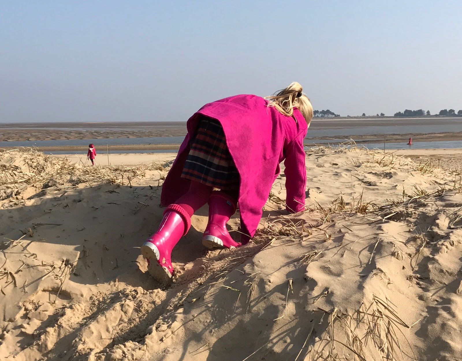 A 5 year old girl in pink coat, tights and wellies climbing up a sand dune on all fours