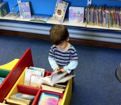 Child in library choosing a book