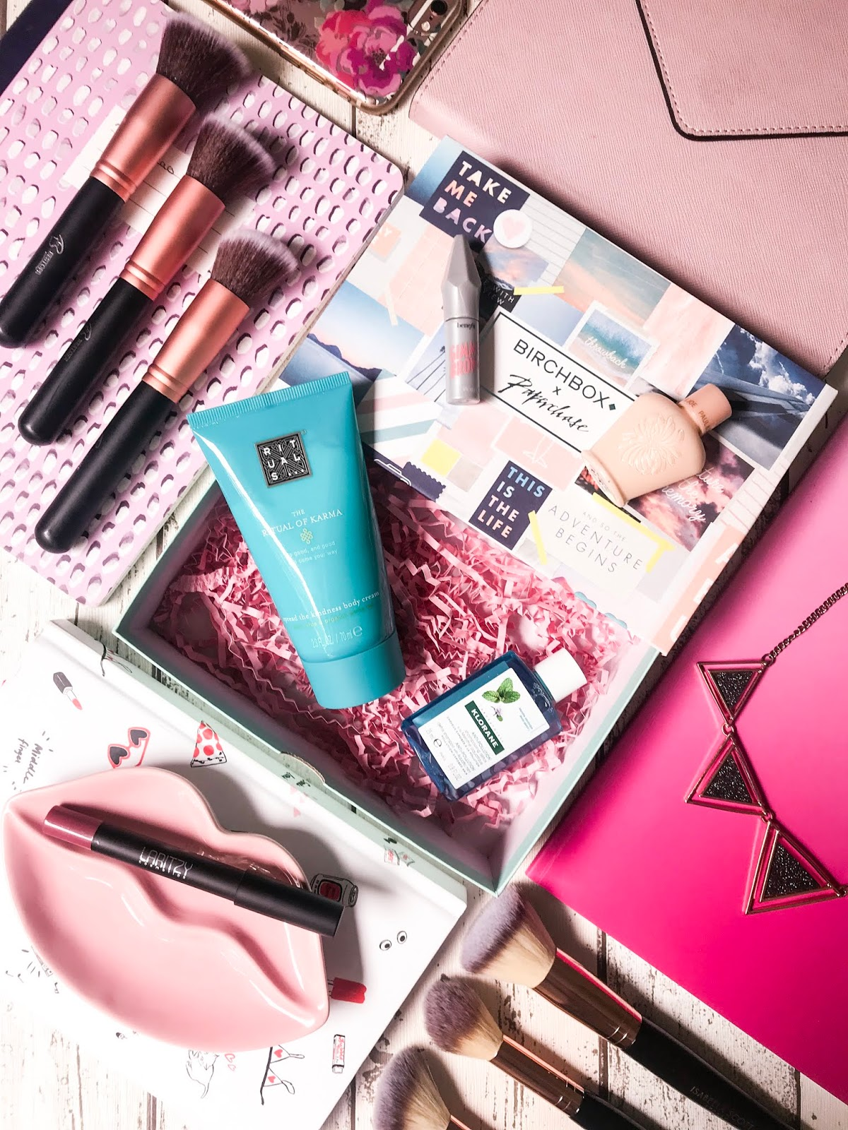 june birchbox flatlay with notebooks, makeup brushes and beauty products
