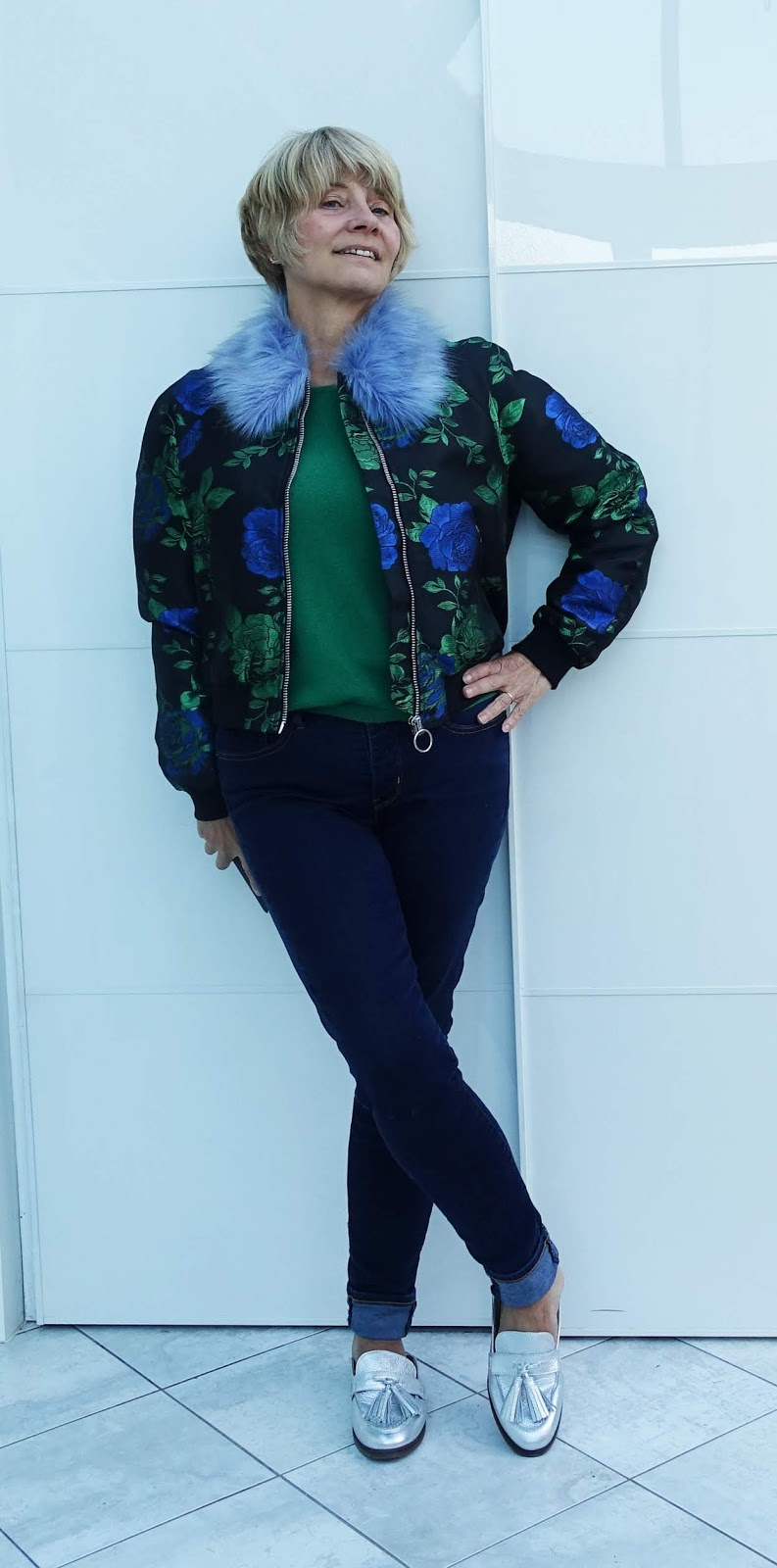 Over 45s blogger Gail Hanlon in green and blue brocade fur trimmed bomber jacket, green jumper, jeans and silver Reagan slip on loafers from Vionic.