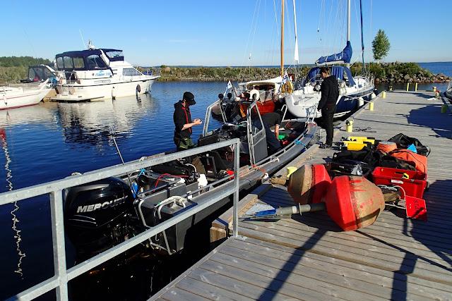 Sukellustarvikkeita laiturilla, venettä lastataan.