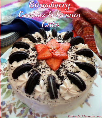 Strawberry Cookies and Cream Cake is studded with crushed cookies and chopped strawberries, then topped with a strawberry cream frosting and sprinkled with more crushed cookies. | Recipe developed by www.BakingInATornado.com | #recipe #dessert