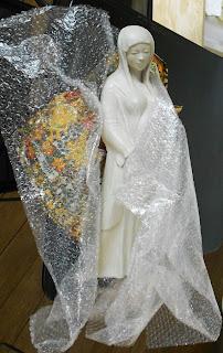 Vierge debout, drapée dans un voile, elle est enceinte