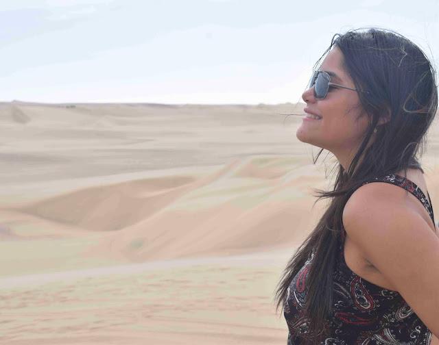 mulher de oculos escuros e cabelo preto de perfil em dunas de areia peruanas