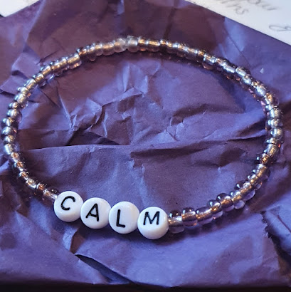 Bracelet made from small round purple beads, and large lettered beads spelling the word calm