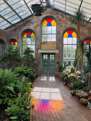 A greenhouse with plants on either side of a tile walkway leading to a green door in a brick wall with stained glass church-like windows. Photo by Renee Fisher on Unsplash