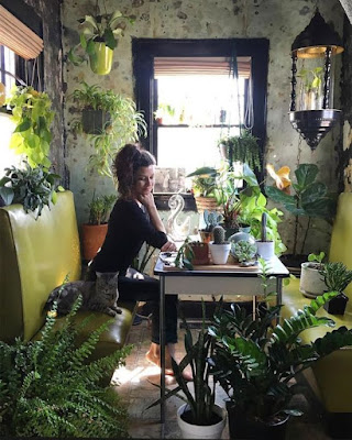 A woman seated on a yellow bench-type seat at a table surrounded by plants.