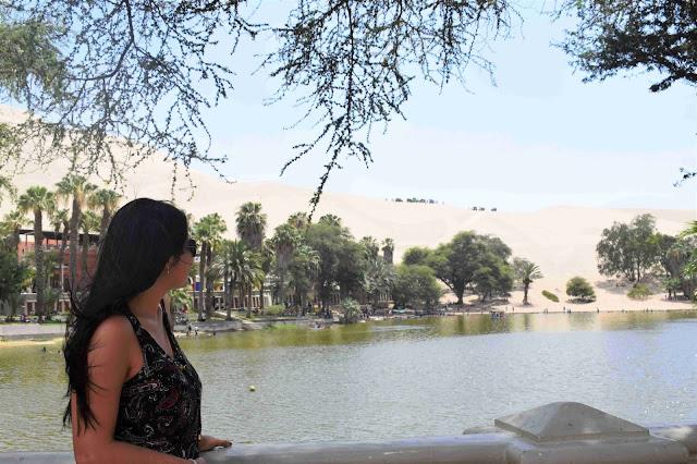 mulher jovem, branca, oculos escuros e macacao preto em uma paisagem de oasis
