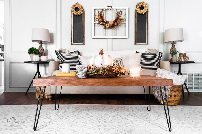 living room sofa and coffee table with dried wheat wreaths, pumpkins and florals