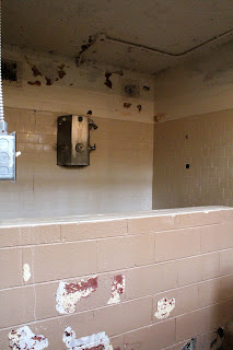Tile half wall with shower heads in a prison