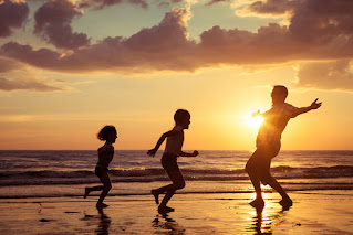 adult man with arms out stretched, two children running towards him, beach, sunset