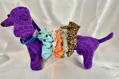 stuffed daschund dog,purple fabric, with scrunchies along its body