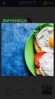 на столе стоит в тарелке приготовленная яичница с колбасой