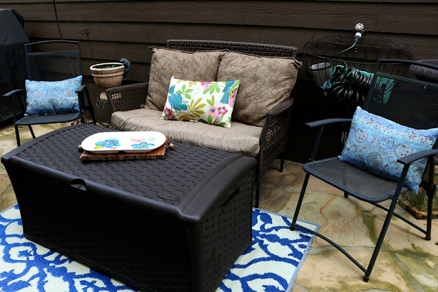 Rugs, pillows and tray add colors of blue, yellow and pink to a neutral patio sitting area