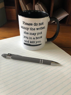 "A mug saying ""Please do not annoy the writer she may put you in a book and kill you"" sitting on top of a note pad next to a pen."
