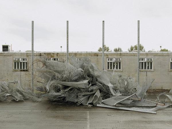 desechos del alambrado frente a una construcción dispuestos de manera artística