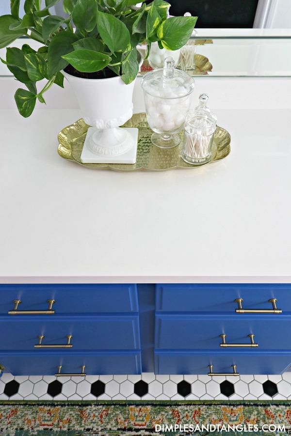 Behr Mondrian Blue, blue painted vanity, black and white hex tile floor, true white quartz countertop