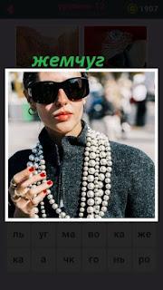 женщина в черных очках и на шее висит ожерелье из жемчуга