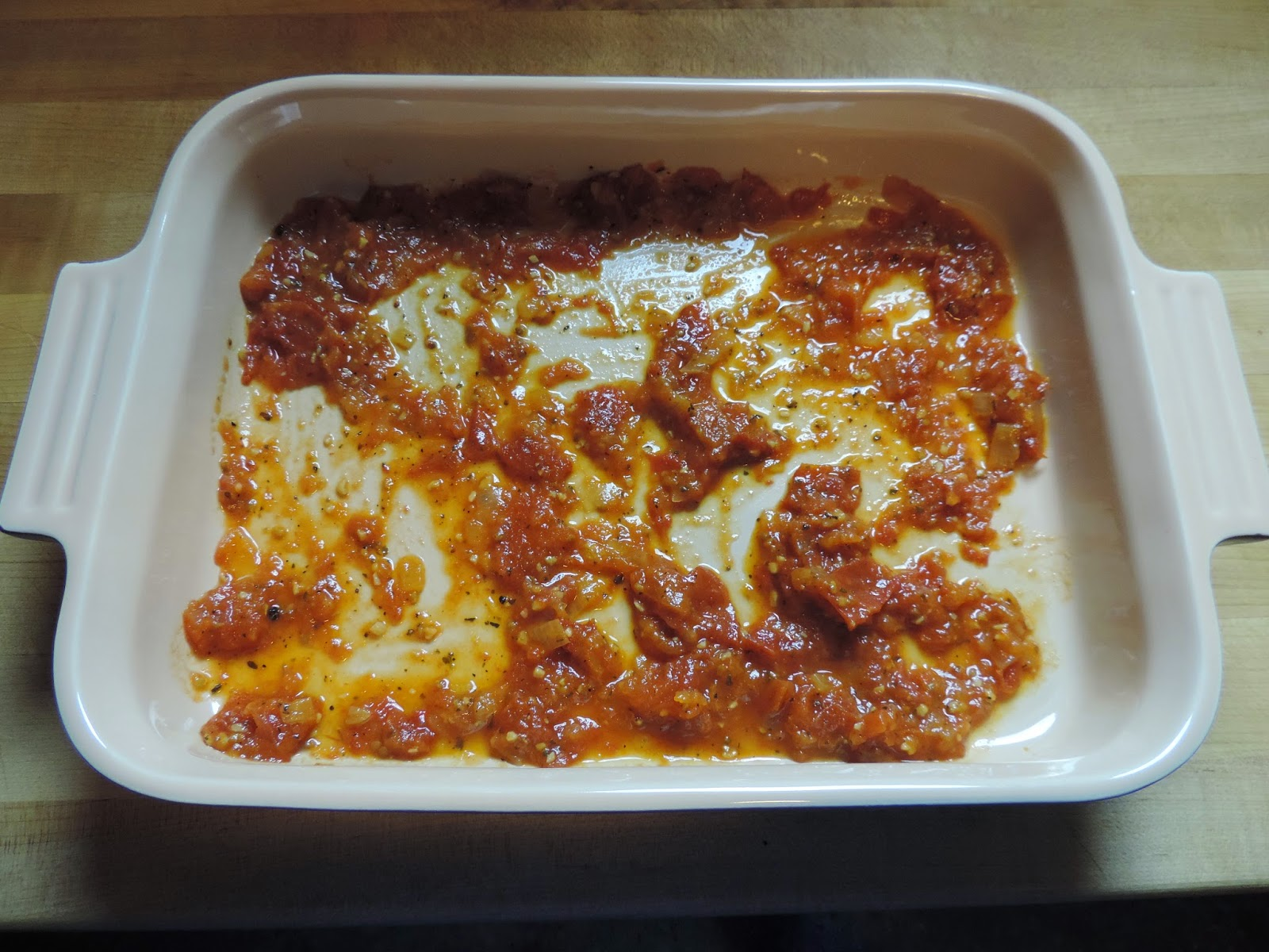 The sauce being added to the bottom of a baking dish.