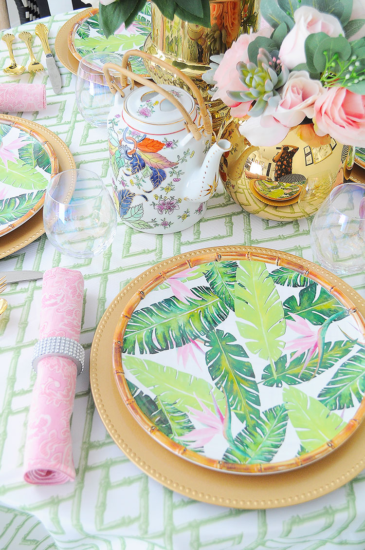 A floral and chinoiserie inspired tablescape and centerpiece design featuring pink peonies, gold accents and bamboo accents.