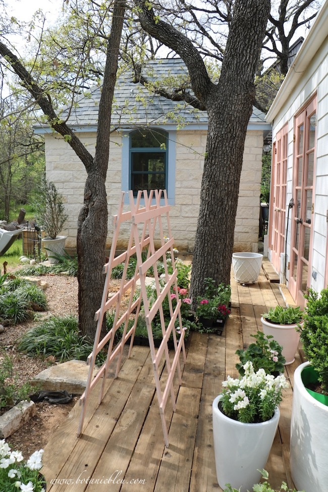 Peach greenhouse new deck opens onto a small garden of gravel, limestone rocks, and lirope grass