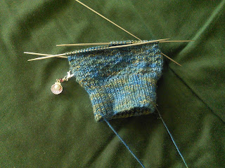 The leg of a textured sock on double-pointed needles.  The yarn is a blue and gold variegated yarn with a small amount of sparkle. There is a a stitch marker clipped into the work, the marker looks like a shell with a purl inside.