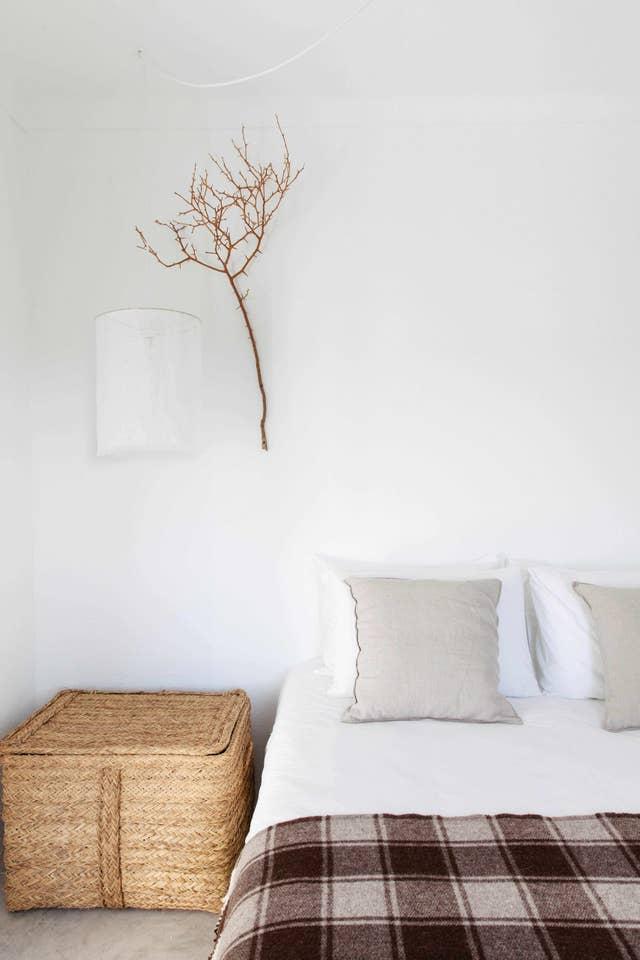 Paredes blancas, líneas sencillas y ramas secas y cesta de mimbre como decoración