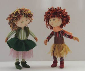 two small dolls with curly hair, embroidered faces and fabric clothing