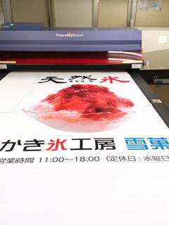 UVインクジェットで大判アルミ複合版に印刷している写真